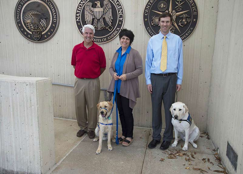 NSA employees Pete Geoghan, Sharon Shoemaker with Zeppelin, and John Barbare with Coby, a service dog.